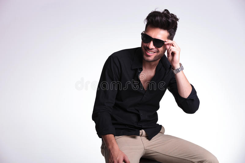 Seated young man holds his sunglasses and smiles royalty free stock images