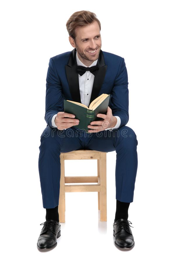 Seated young man smiling with a book opened in hand royalty free stock photos