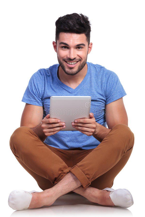 Seated young man with tablet pad smiling royalty free stock images