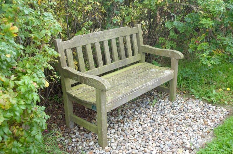 Seater två parkerar bänkuppsättningen på grus med häcken bakom royaltyfri fotografi