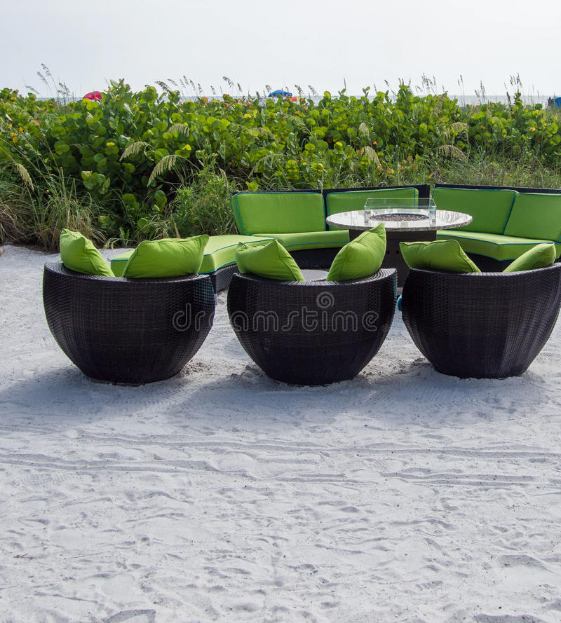 Seating on the beach at st petersburg beach, fl. Wicker chairs and sofa with green cushions and fire pit table on white sandy beach overlooking beach and sea stock photos