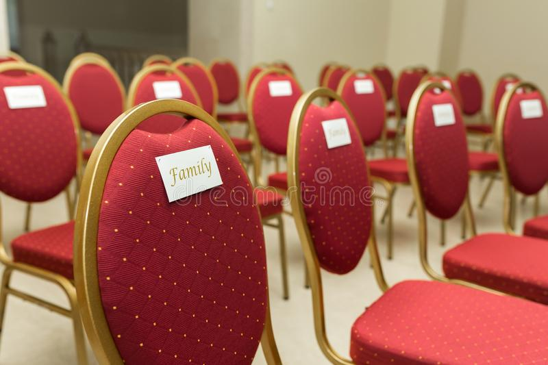 Seating chairs for guests at a wedding ceremony in the festive hall. Chairs upholstered in red cloth nameplate family.  stock images