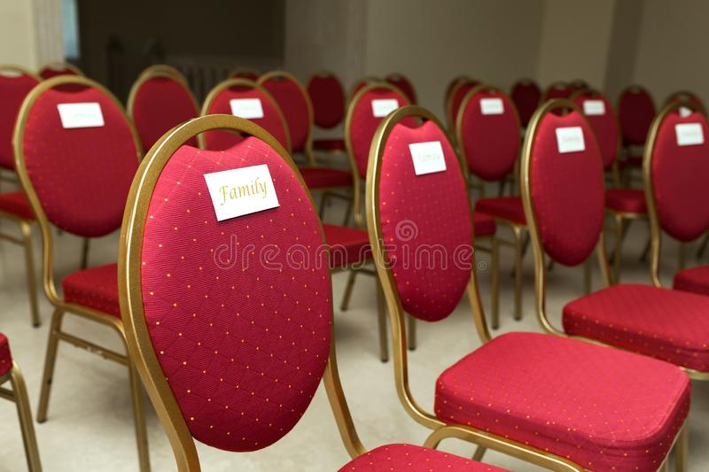 Seating chairs for guests at a wedding ceremony in the festive hall. Chairs upholstered in red cloth nameplate family.  stock image