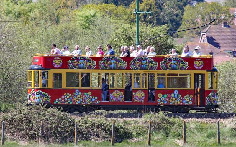 SEATON, ДЕВОН, АНГЛИЯ - 22-ОЕ МАЯ 2012: Перемещения украшенные красные трамвая вдоль трамвая Seaton на своем пути к Colyford Оно  стоковые фотографии rf