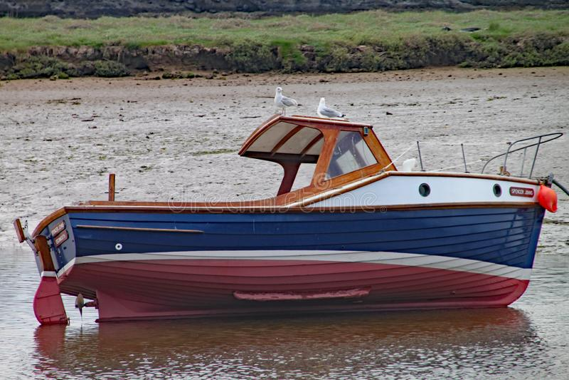 SEATON, DEVON, INGLATERRA - 22 DE MAYO DE 2012: Un pequeño barco de pesca miente en su lado durante la bajamar en el estuario del fotos de archivo
