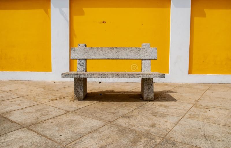 Seats against yello wall in Pondicherry, India. Seats against wall in Pondicherry, India stock photography