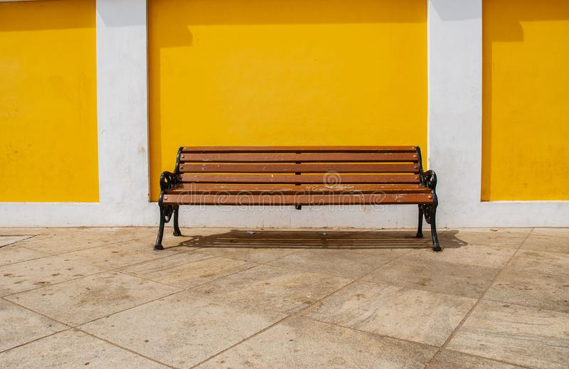 Seats against yello wall in Pondicherry, India. Seats against wall in Pondicherry, India royalty free stock image