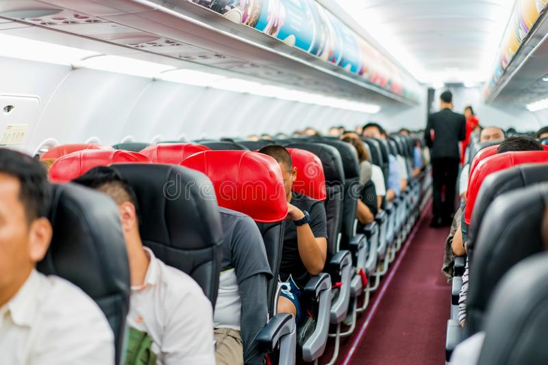 Seats in the airplane and passenger sitting all area waiting for the plane taking off from runway royalty free stock images