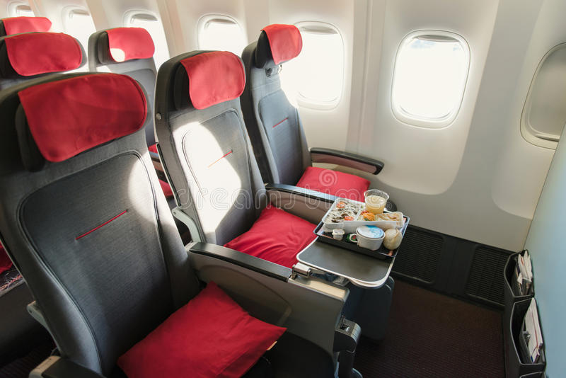 Seats on board of airplane. Cabin of economy class with screens royalty free stock images