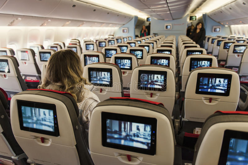 Seats on board of airplane. Cabin of economy class with screens royalty free stock photos