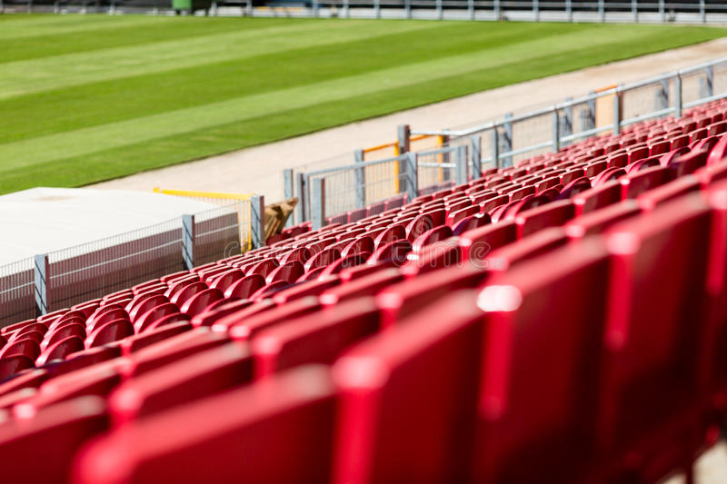 Seats at stadium. Rows of red plastic seats at large soccer stadium royalty free stock photos