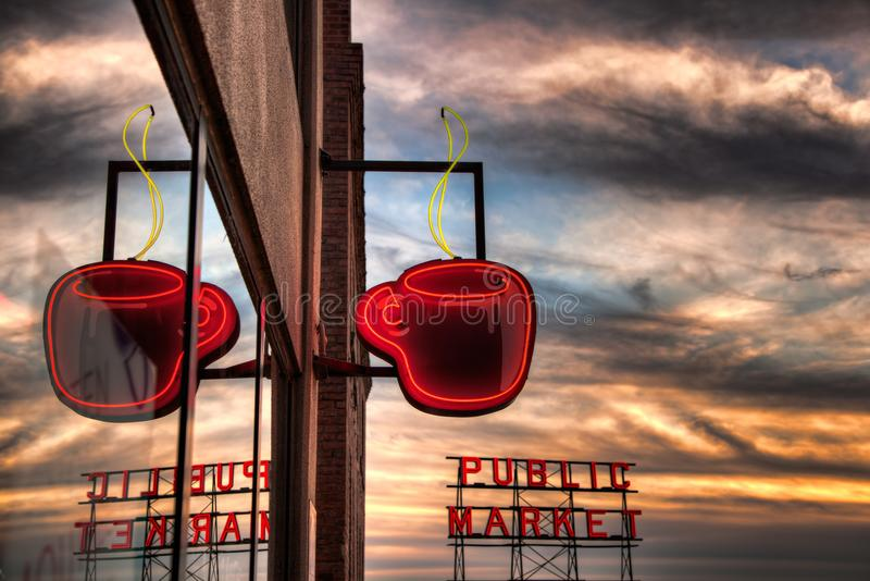 Seattle Coffee Cup. SEATTLE, WA - SEPTEMBER 21, 2011: Neon coffee cup and Pikes Place Market sign at sunset. Seattle is associated with coffee, as the birthplace stock photos