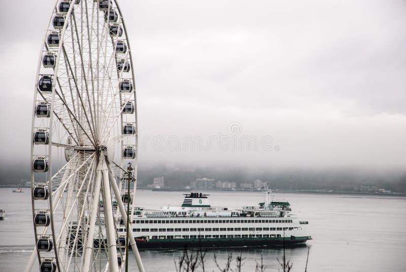 Seattle färja som förbigår det stora hjulet på dimmig dag arkivbilder