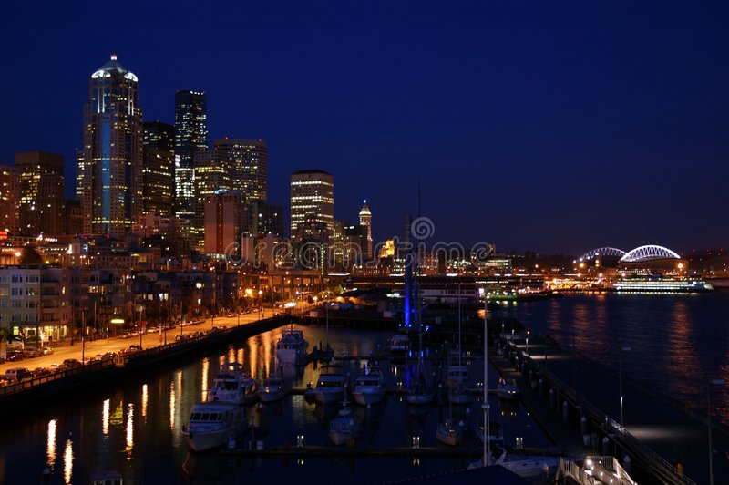 Seattle in the night. A lovely view of the night-lights and skyline of Seattle with reflections of the scene on the waterfront royalty free stock images