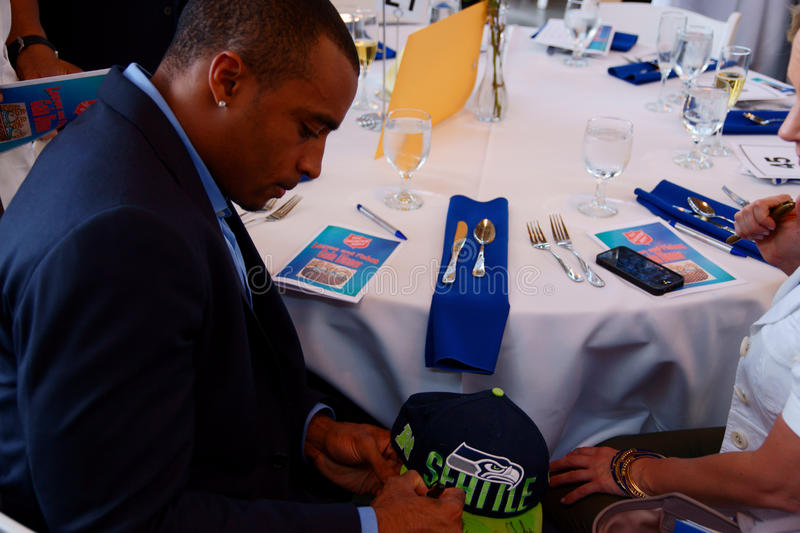 Seattle Seahawks Doug Baldwin. Doug Baldwin, wide receiver for the Seattle Seahawks autographs memorabilia at The Salvation Army in Tacoma Fishes and Loaves royalty free stock photography