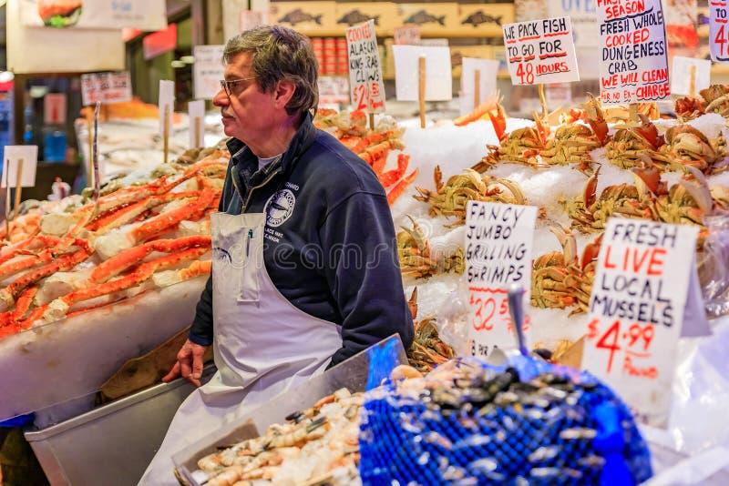 Seattle, Stany Zjednoczone - Listopadu Fishmonger przy kramem z świeżym owoce morza lubi kraba, garneli i mussels dla sprzedaży,  zdjęcie stock