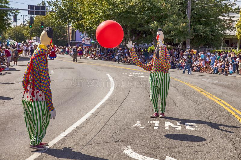 Two Clowns Toss A Red Ball. SEATTLE, WA - JUNE 22, 2013: Two clowns play catch with a red ball in the middle of the street during the Fremont Summer Solstice royalty free stock photos