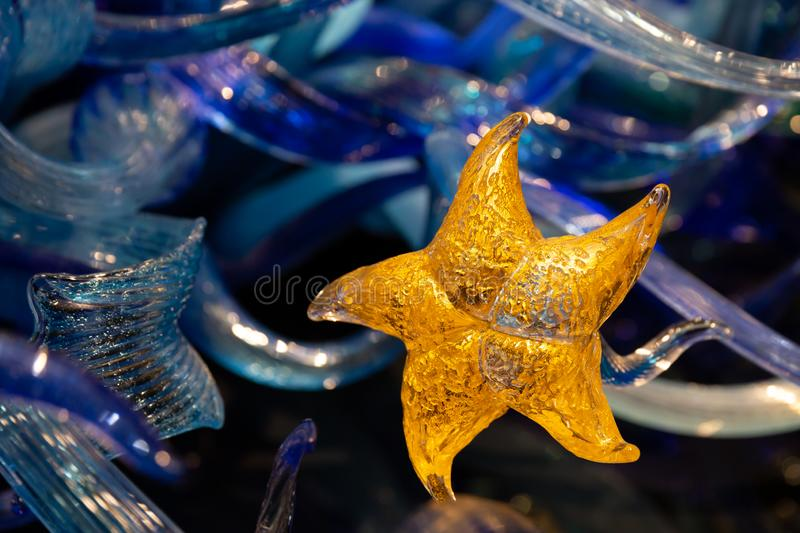 Seattle, Washington - 10.02.2018: Chihuly Garden and glass exhibition. Golden star, closeup element of Sealife Tower sculpture.  royalty free stock photography