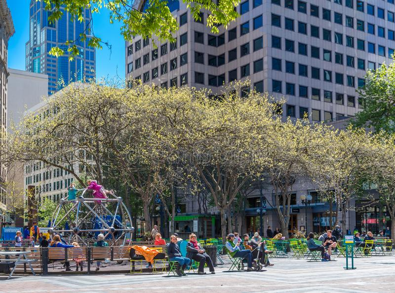 People at Westlake Park. SEATTLE, WASHINGTON - May 13, 2017: Logging was Seattle`s first major industry, but this has long been replaced by shipping, tourism stock photography