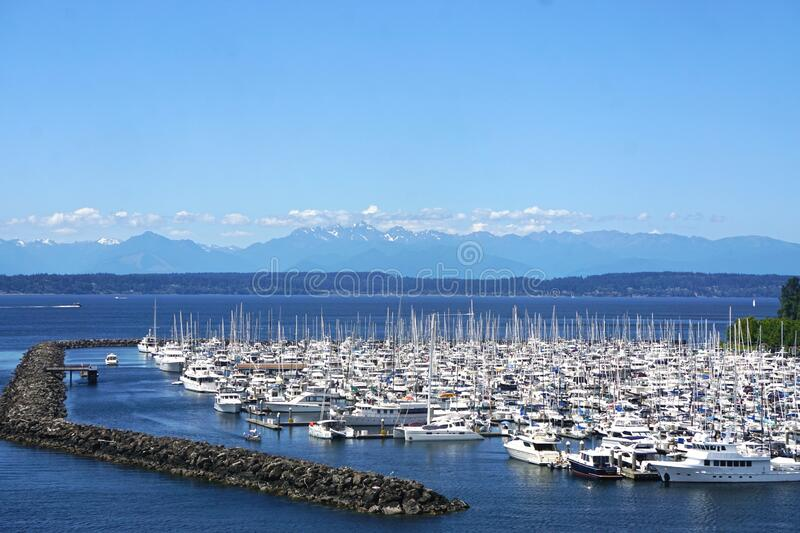 Seattle, Washington, USA: Marina filled with sailboats on the deep blue waters of Puget Sound. With snow-capped mountains in the distance stock photos