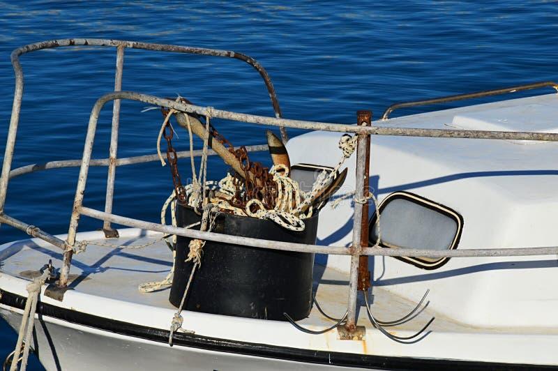 Seau avec ancrages, chaîne rouillée et cordes attachées à une grille en acier devant le bateau de pêche blanc couvert photographie stock libre de droits