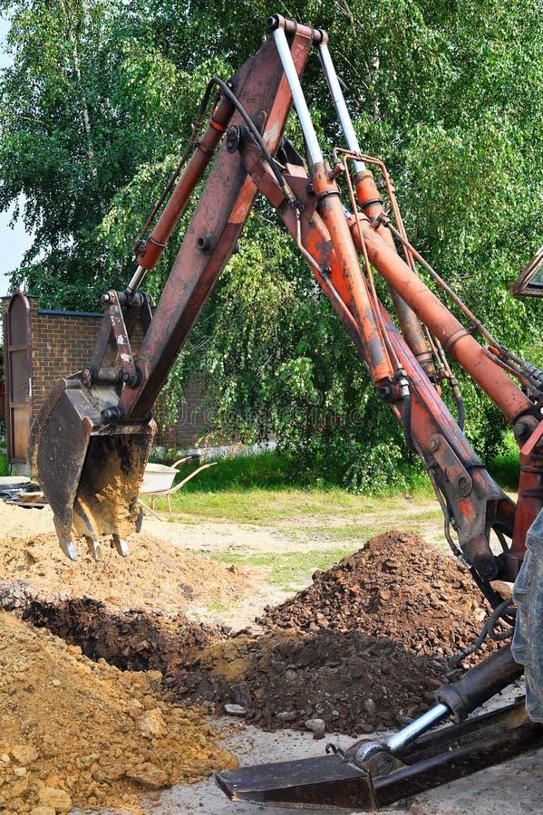 Seau d'excavatrice creusant un fossé dans l'au sol de saleté photos stock