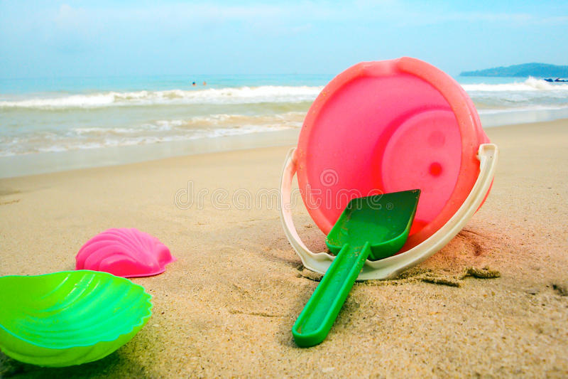 Seau du ` s d'enfants et moules colorés sur la plage dans le sable photographie stock