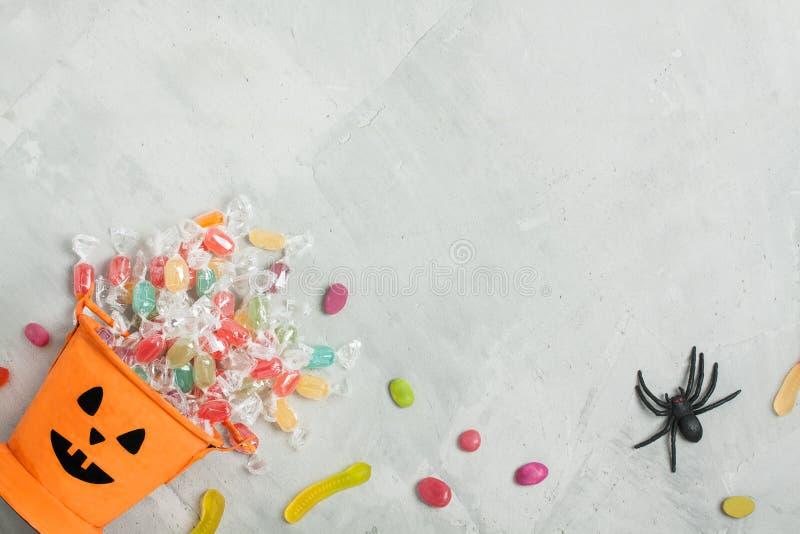 Seau orange de Halloween avec des sucreries, des jujubes, et l'araignée en caoutchouc image stock