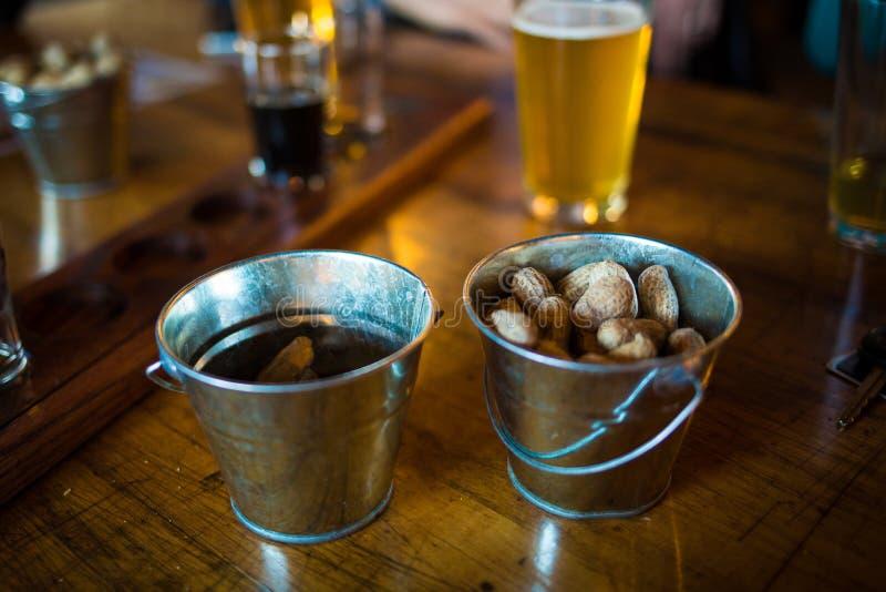 Seaux de barre avec les arachides et la bière crues image libre de droits