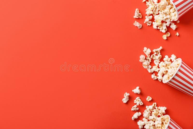 Seaux de papier avec le maïs éclaté dispersé savoureux sur le fond de couleur photographie stock