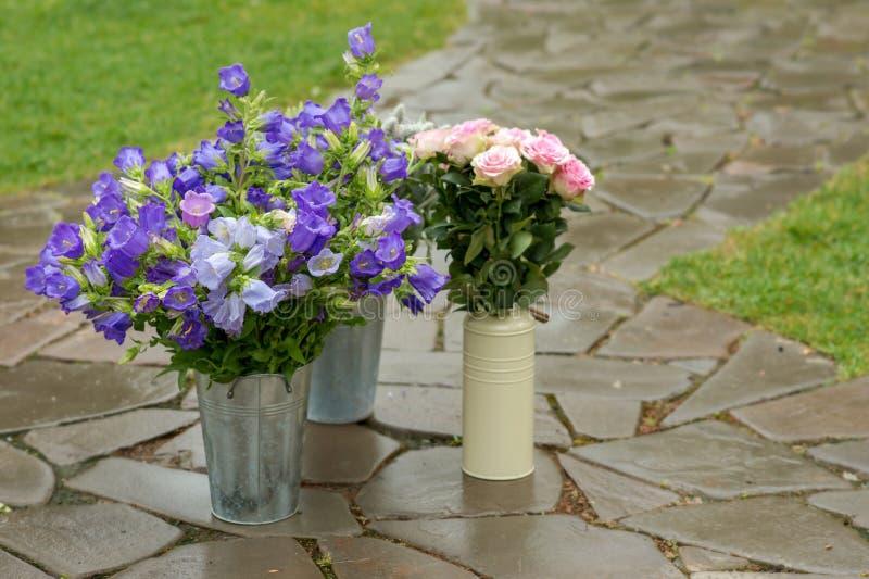 Seaux et boîtes avec des fleurs Cloches et rose bleues de rose photographie stock
