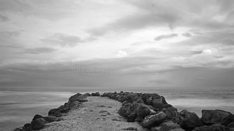 Seawall Grayscale long exposure shot. A long exposure shot of a rock seawall processed to grayscale. Image taken on an early overcast morning in Burleigh Heads royalty free stock images