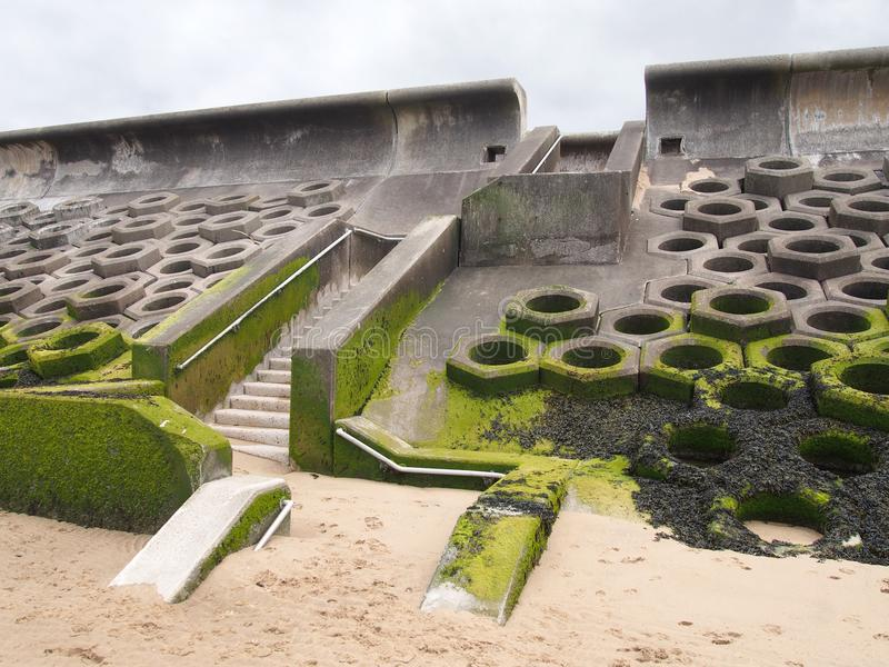 Seawall south of blackpool constructed of concrete honeycomb type structures with steps leading to the beach covered in tidal. The seawall south of blackpool stock photography