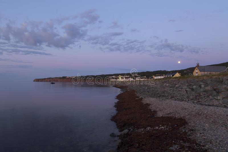 Seaweed on pebbled beach with low full moon seen over the famous Percé village bay. During a beautiful summer dawn, Quebec, Canada royalty free stock image