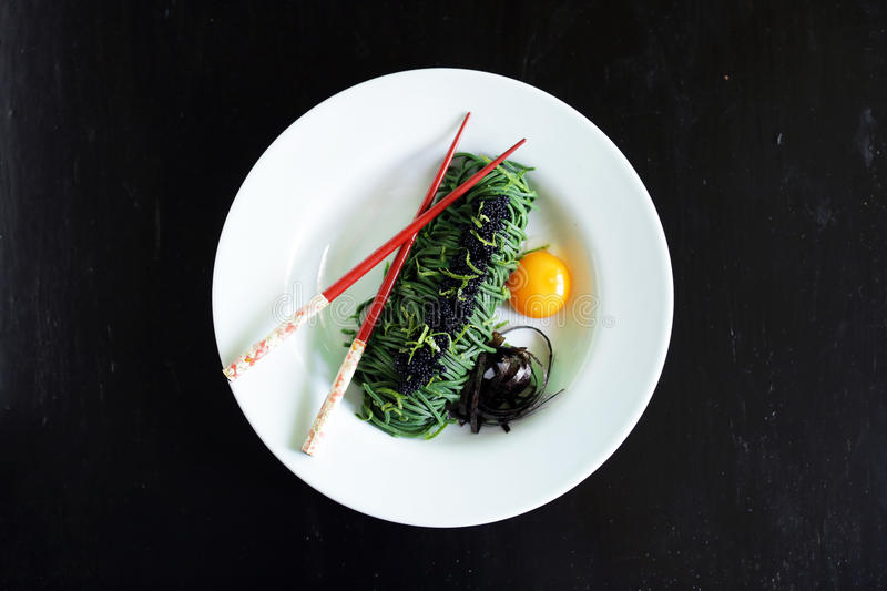 Seaweed spaghetti noodles with egg yolk, nori and caviar stock photos