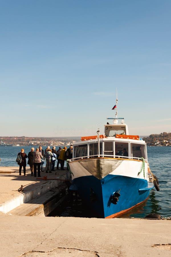 SEBASTOPOLI, RUSSIA - NOVEMBRE 4,2018: Il gruppo di turisti si siede su una barca per un giro del mare sulla baia di Mar Nero fotografia stock libera da diritti