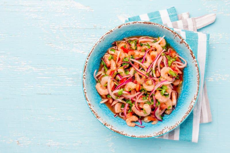 Sebiche équatorien de ceviche de crevettes avec des tomates dans la cuvette bleue, fond bleu en bois Ecuadorian traditionnel colo photographie stock