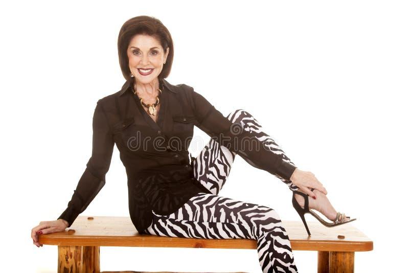 Sebraflåsanden för äldre kvinna sitter på att le för bänk royaltyfri foto