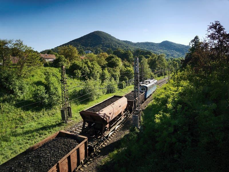 Sebuzin, Tschechische Republik - 19. Mai 2017: Güterzug mit Nachmittags-Frühlingslandschaft der Kohle laufender lizenzfreie stockbilder