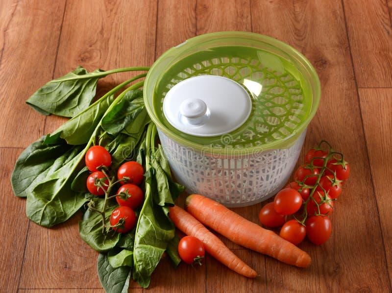 Secador centrífugo para la ensalada con las verduras alrededor fotos de archivo