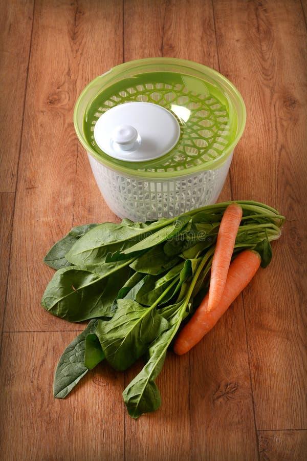 Secador centrífugo para la ensalada con las verduras alrededor fotos de archivo libres de regalías