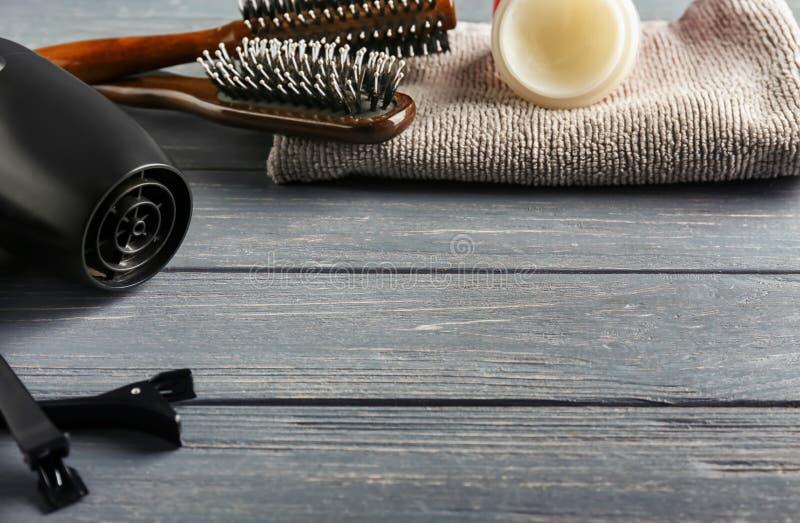 Secador con los cepillos, los clips, los cosméticos y la toalla en la tabla de madera imagen de archivo