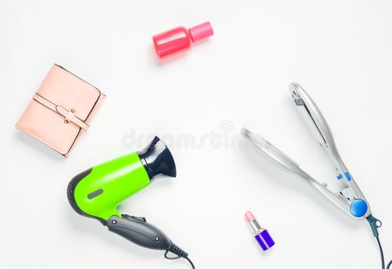 Secador de pelo, hierro del pelo, lápiz labial, botella de perfume, monedero aislado en el fondo blanco Cosméticos, accesorios y  imagen de archivo