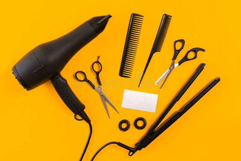 Secador, peine y tijeras de pelo negro en fondo de papel amarillo Visión superior imagenes de archivo