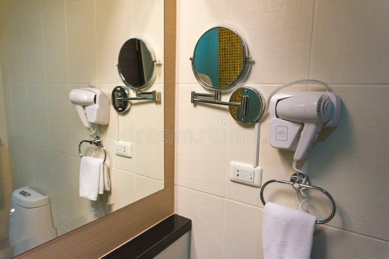 Secador y espejo de pelo blanco en la pared en cuarto de baño foto de archivo libre de regalías