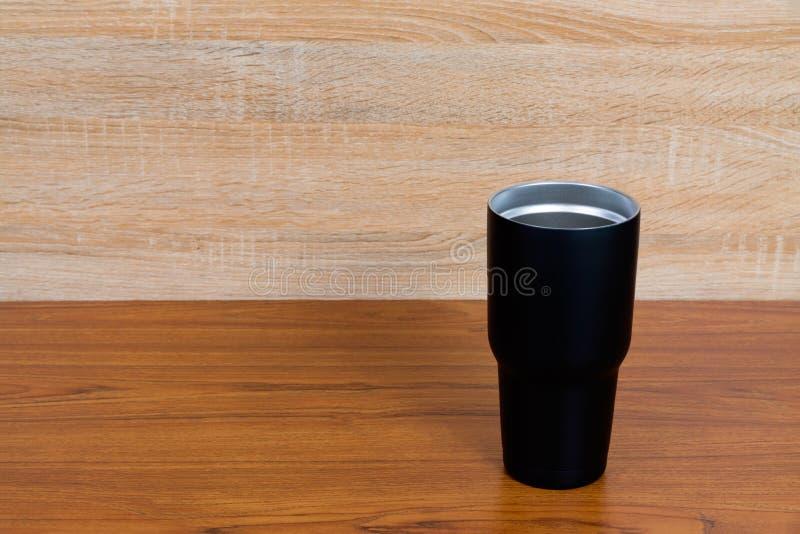 Secadora de roupa de aço inoxidável da cor preta ou copo do armazenamento frio na madeira fotografia de stock royalty free