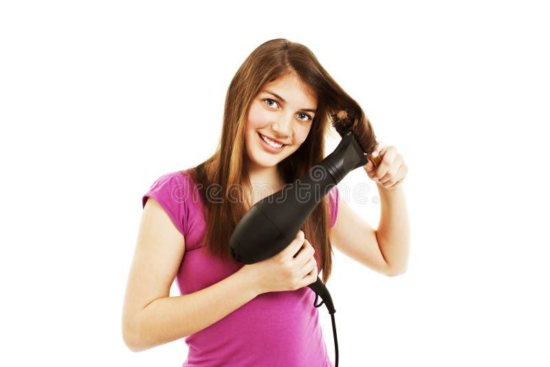 Secagem bonita da mulher nova seu cabelo com secador fotos de stock