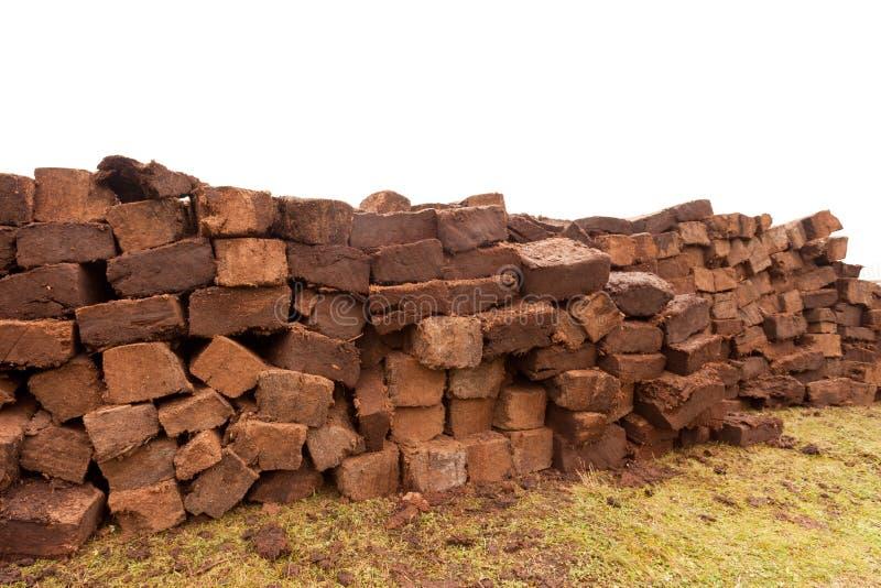 Secagem empilhada dos cortes do carvão amassado do relvado da turfa do pântano imagem de stock royalty free