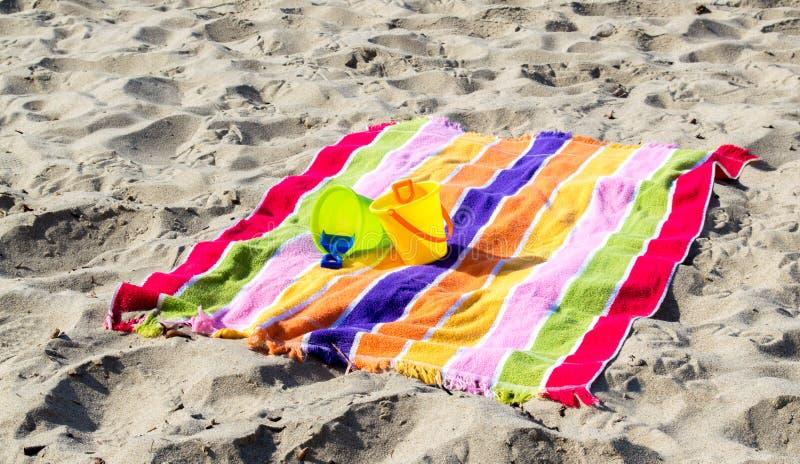 2 secchi e pale della sabbia del ` s del bambino su un asciugamano di spiaggia a strisce immagine stock libera da diritti