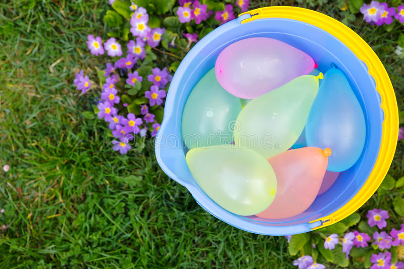 Secchio blu con i palloni di acqua immagini stock